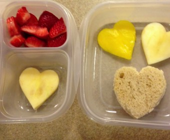 Heart shaped pb & j, heart shaped apple slices, and a heart shaped yellow pepper slice, strawberries. Yogurt smoothie in red squeeze tube and a piece of dark chocolate as a special treat! All ingredients organic.