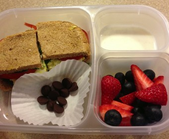 Egg salad on homemade multi-grain bread with spinach and tomatoes, strawberries and blueberries, vanilla bean yogurt and chocolate chips. All ingredients organic.