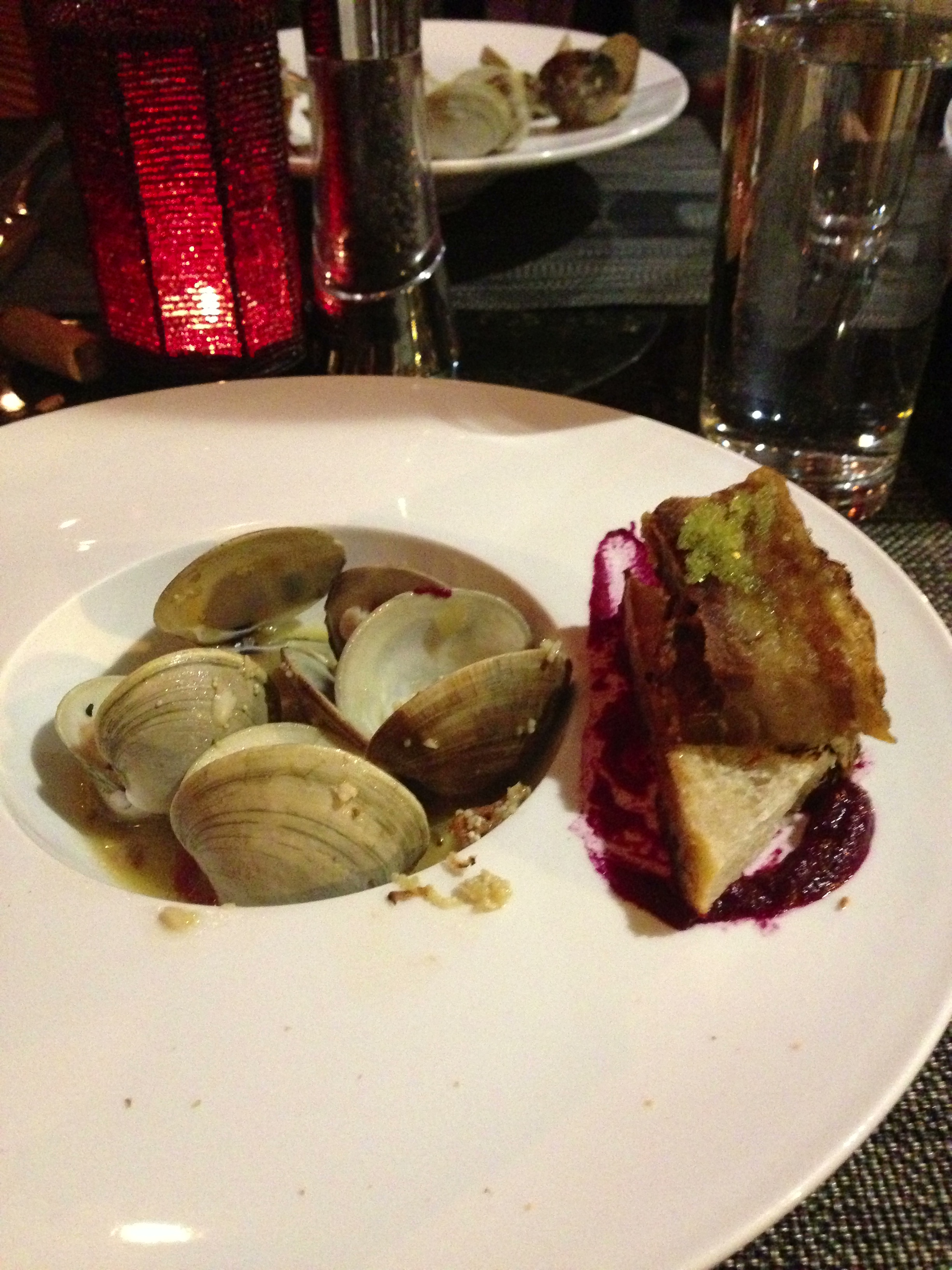 Steamed clams in wasabi and smoked bacon sauce. Served with pork belly and ciabatta over beet puree.